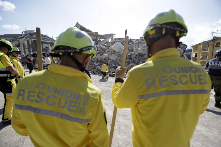 Members of the 'Rescue Team of Ram Union', from the region of Zhejiang, China, prepare to take part in rescue operations, in Amatrice, Friday, Aug. 26, 2016 two days after an earthquake. Rescue crews have raced against time since a devastating earthquake leveled three towns in central Italy last Wednesday Aug. 23, leaving hundreds dead. (AP Photo/Andrew Medichini)