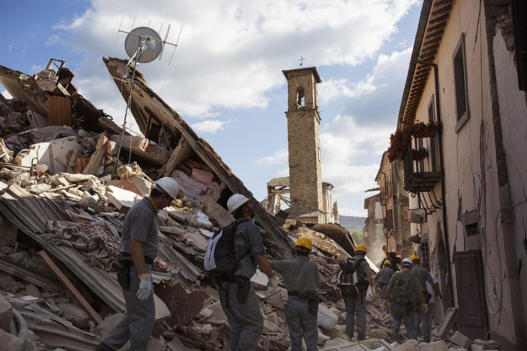 Rescuers make their way through rubble in Accumoli, central Italy, Friday, Aug. 26, 2016, two days after an earthquake. Strong aftershocks rattled residents and rescue crews alike Friday as hopes began to dim that rescuers would find any more survivors from Italy's earthquake. (Roberto Salomone/ANSA via AP)