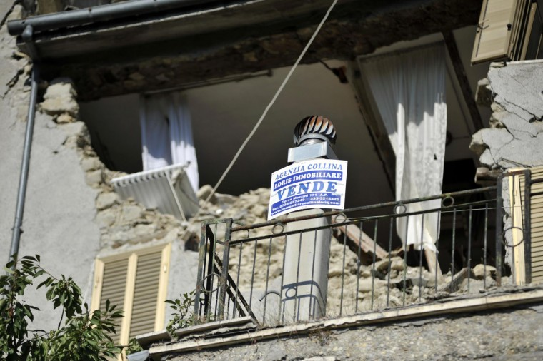 "A real estate agency's sign reading in Italian ""On Sale"" hangs from the balcony of a partially collapsed house in Arquata del Tronto, central Italy, Friday, Aug. 26, 2016, two days after an earthquake. Strong aftershocks rattled residents and rescue crews alike Friday as hopes began to dim that rescuers would find any more survivors from Italy's earthquake. (Cristiano Chiodi/ANSA via AP)"