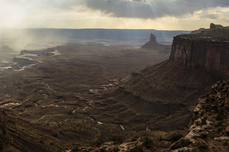 In this Wednesday, Aug. 24, 2016 photo, sunlight filters through the clouds over Canyonlands National Park as seen from Orange Cliffs Overlook near Moab, Utah. The National Park Service marks its 100th anniversary on Thursday, Aug. 25, 2016. (Chris Detrick/The Salt Lake Tribune via AP)