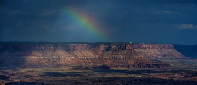 In this Wednesday, Aug. 24, 2016 photo, a rainbow appears in the distance as seen from Grand View Point in the Island in the Sky District at Canyonlands National Park near Moab, Utah. the National Park Service marks its 100th anniversary on Thursday, Aug. 25, 2016. (Chris Detrick/The Salt Lake Tribune via AP)
