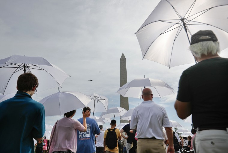 People assemble for a living version of the National Park Service's iconic Arrowhead emblem, near the Washington Monument on the National Mall in Washington, Thursday, Aug. 25, 2016. More than 1,000 participants used brown, green and white umbrellas to create the emblem during an event that took place on the 100th anniversary of the creation of the National Park Service. They also posed for a group photo that was being taken from a helicopter hovering overhead. (AP Photo/Pablo Martinez Monsivais)