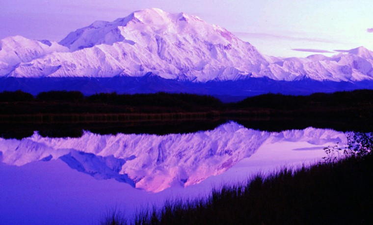 FILE - In this undated file photo, the sun sets as Mount McKinley casts its reflection on Reflection Pond at the west end of Denali National Park Road a few miles east of Camp Denali in Denali Park, Alaska. In August, 2015, the government changed the name of North America's tallest peak from Mount McKinley to Denali. (AP Photo/Al Grillo, File)