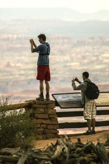 In this Wednesday, Aug. 24, 2016 photo, Neel Largerom, left, and Laurent Hamon, both of France, take pictures at Grand View Point in the Island in the Sky District at Canyonlands National Park near Moab, Utah. The National Park Service marks its 100th anniversary on Thursday, Aug. 25, 2016. (Chris Detrick/The Salt Lake Tribune via AP)