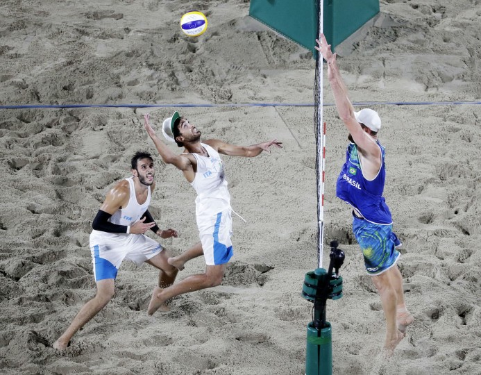 Italy's Daniele Lupo, center, goes up to spike the ball against Brazil's Alison Cerutti, right, as teammate Paolo Nicolai, left, looks on during the men's beach volleyball gold medal match at the 2016 Summer Olympics in Rio de Janeiro, Brazil, Friday, Aug. 19, 2016. (AP Photo/David Goldman)