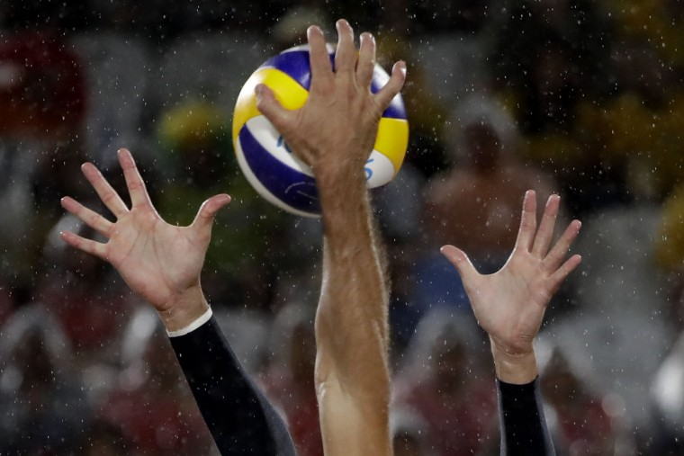 Italy's Paolo Nicolai keeps both hands up to defend as Brazil's Bruno Oscar Schmidt hits during the men's beach volleyball gold medal match at the 2016 Summer Olympics in Rio de Janeiro, Brazil, Friday, Aug. 19, 2016. (AP Photo/Marcio Jose Sanchez)