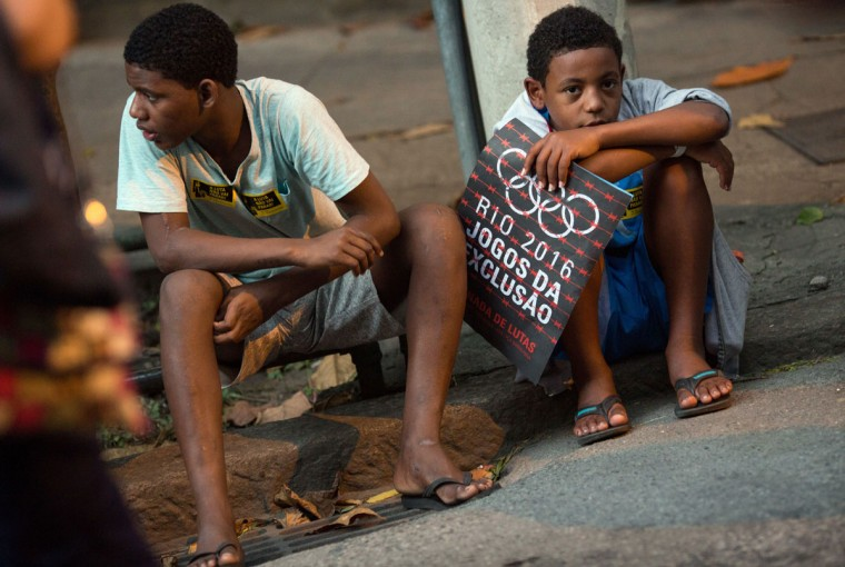"Two boys sit on the sidewalk as they attend a protest against the Rio's 2016 Summer Olympics near the Maracana stadium before the opening ceremony of the Olympics in Rio de Janeiro, Brazil, Friday, Aug. 5, 2016. The sign reads in Portuguese ""Rio 2016 Games of exclusion."" (AP Photo/Mauro Pimentel)"