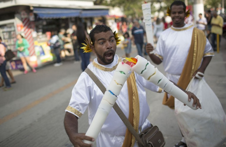 A man selling plastic Olympic torches jokes as he waits for costumers while waiting for the Olympic torch on its way to Rio de Janeiro for the opening ceremony of Rio's 2016 Summer Olympics, in Niteroi, Brazil, Tuesday, Aug. 2, 2016. The three-month torch relay across Brazil will end at the opening ceremony on Aug. 5, in Maracana stadium. (AP Photo/Leo Correa)