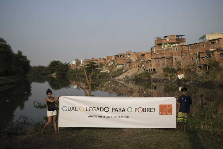 People pose for photos holding a banner that reads in Portuguese 'What's the legacy to the poor?' as part of a protest organized by the NGO 'Rio de Paz,' or Rio of Peace, in the the Mandela slum of Rio de Janeiro, Brazil, Tuesday, Aug. 9, 2016. Members of the NGO walked through slums asking residents about the Olympic legacy; the same areas visited by members of the International Olympic Committee in 2014, where they asked the IOC to request their city government make improvements in their neighborhoods. (AP Photo/Felipe Dana)