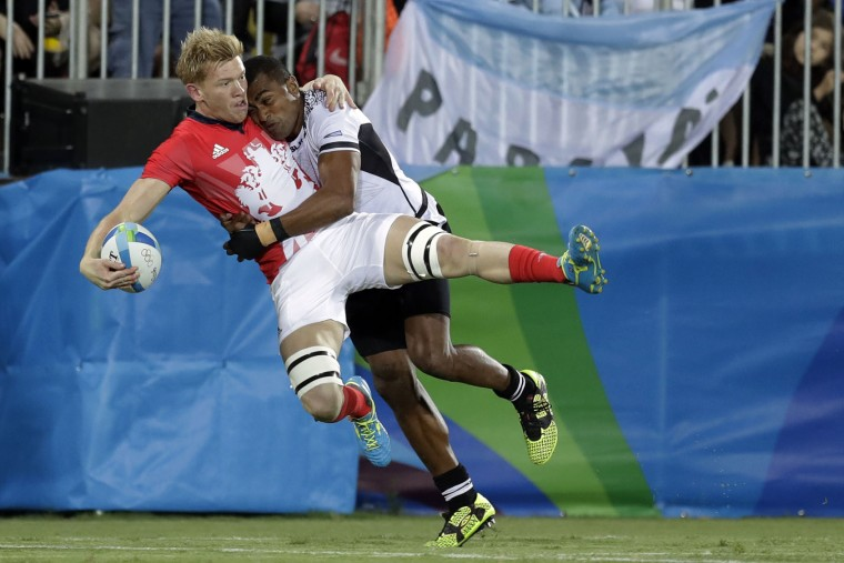 Britain's Sam Cross, left, is tackled by Fiji's Apisai Domolailai, during the men's rugby sevens gold medal match at the Summer Olympics in Rio de Janeiro, Brazil, Thursday, Aug. 11, 2016. (AP Photo/Themba Hadebe)
