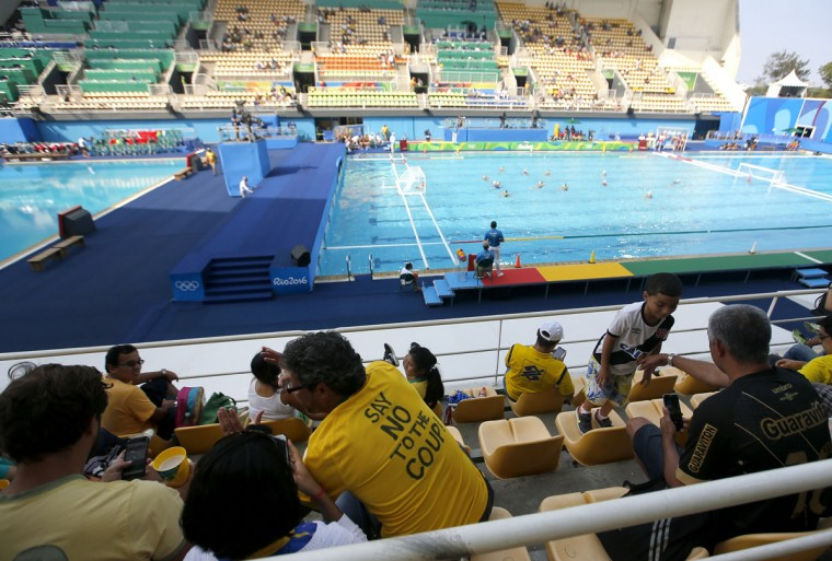 "A fan with a Brazil national football team jersey with the text that reads ""Say No To The Coup"" written on it, watches a women's water polo preliminary round match at the Maria Lenk Aquatics Centre in Rio de Janeiro, Brazil, Tuesday, Aug. 9, 2016. A court ruling banning the removal of protesters from Olympic venues is fueling debate on whether Brazil's political crisis should be kept out of the athletic competition. The ruling Monday came after a Brazilian Olympic volunteer defaced his official credentials to demonstrate his opposition to orders to escort out of stadiums fans holding up signs against interim President Michel Temer. (AP Photo/Eduardo Verdugo)"