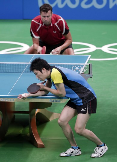 Jun Mizutani, of Japan, bottom, serves to Vladimir Samsonov, of Belarus, during the men's table tennis bronze medal match at the 2016 Summer Olympics in Rio de Janeiro, Brazil, Thursday, Aug. 11, 2016. (AP Photo/Mark Humphrey)