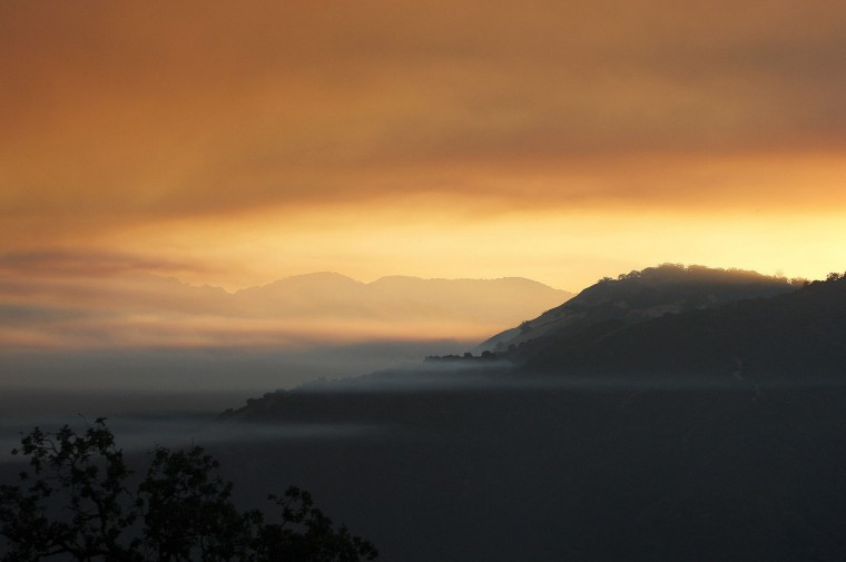 In this photo taken Tuesday, Aug. 2, 2016, smoke heads west from the Soberanes Fire near Cachagua, Calif. A wildfire north of Big Sur near California's Central Coast has grown again overnight after burning for nearly two weeks. The fire has scorched more than 79 square miles and is less than 30 percent contained. It has destroyed 57 homes and is threatening another 2,000 structures. (Vern Fisher/Monterey Herald via AP)