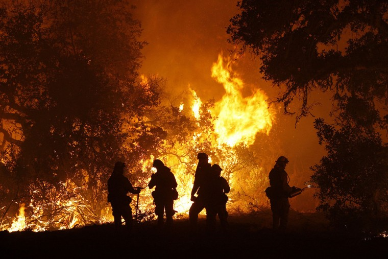 In this photo taken Tuesday, Aug. 2, 2016, Cal Fire captain Gino DeGraffenreid monitors a firing operation with his crew of firefighters west of Cachagua, Calif. A wildfire north of Big Sur near California's Central Coast has grown again overnight after burning for nearly two weeks. The fire has scorched more than 79 square miles and is less than 30 percent contained. It has destroyed 57 homes and is threatening another 2,000 structures. (Vern Fisher/Monterey Herald via AP)