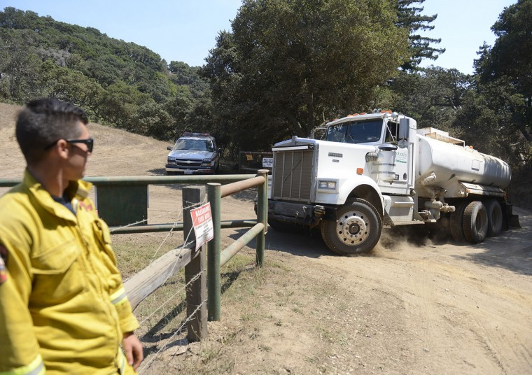 Carmel Hill Cal Fire firefighter mans a gate as a support water tanker heads into the El Sur Ranch near the top of the Old Coast Road as firefighters battle a wildfire in Big Sur, Calif., on Thursday, Aug. 4, 2016. A stubborn wildfire north of Big Sur near California's Central Coast has grown after burning for nearly two weeks in steep, forested ridges. (David Royal/The Monterey County Herald via AP)