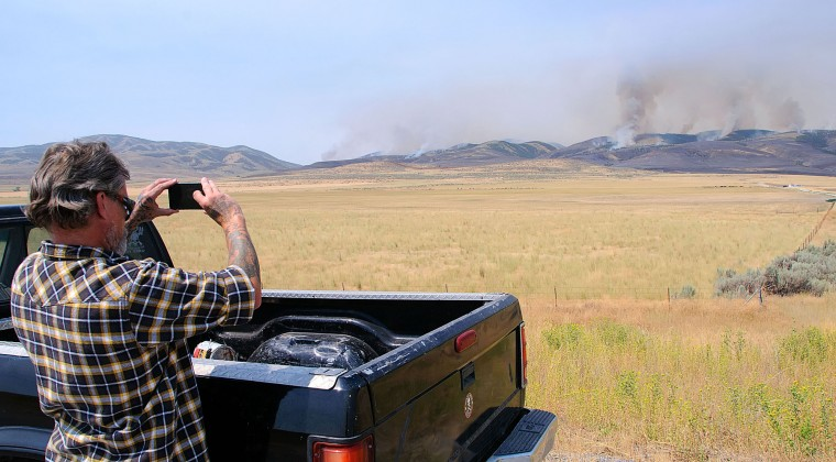 Danny Nickle takes a picture of a wildfire Thursday, Aug. 4, 2016, near Plymouth, Utah. Officials say more than two dozen large wildfires are burning in the West. (Eli Lucero/The Herald Journal via AP)