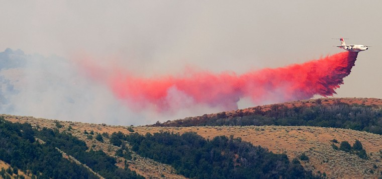 A plane aids in firefighting efforts on the ridgeline of a wildfire Thursday, Aug. 4, 2016, near Plymouth, Utah. Officials say more than two dozen large wildfires are burning in the West. (Eli Lucero/The Herald Journal via AP)