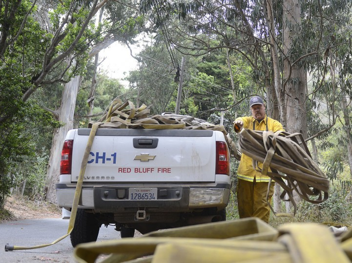 Red Bluff Fire strike team leader Ray Barber unloads large piles of hose that was removed from Long Ridge near the Gate at Palo Colorado Canyon as firefighters battle a wildfire in Big Sur on Thursday, Aug. 4, 2016. Officials say more than two dozen large wildfires are burning in the West. Hot, windy weather has made conditions difficult for firefighters as the blazes destroy homes and force evacuations. (David Royal/The Monterey County Herald via AP)