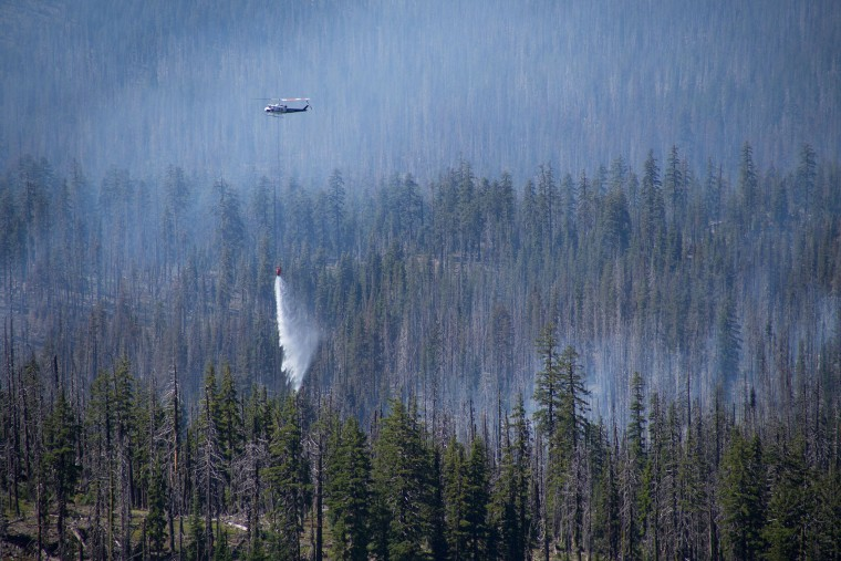 A helicopter drops water on a wildfire southwest of Crater Lake, Ore., Thursday, Aug. 4, 2016. A wildfire burning southwest of Crater Lake prompted an evacuation warning for some parts of Crater Lake National Park. (Brian Davies/The Register-Guard via AP)