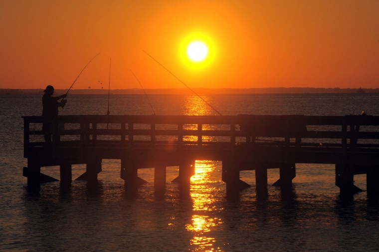 A fisherman is silhouetted by the sunrise at Romancoke Pier. Kent Island has much to offer visitors. The largest island in Maryland boasts fishing piers, beaches, water trails, nature parks, historic buildings, restaurants with bay views, and many other attractions. (Algerina Perna/Baltimore Sun)
