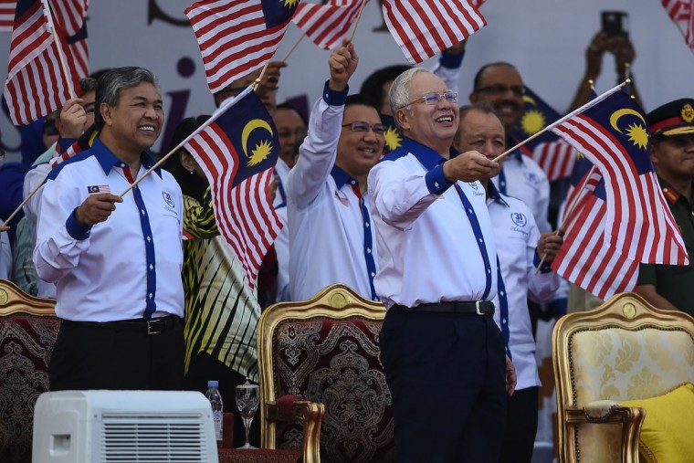 Malaysia's Prime Minister Najib Razak (right) and his deputy Ahmad Zahid Hamidi (left) wave national flags during the 59th National Day celebrations at Independence Square in Kuala Lumpur on August 31, 2016. Malaysia celebrated its 59th National Day to commemorate the independence of the Federation of Malaya from British rule in 1957. (MOHD RASFAN/AFP/Getty Images)
