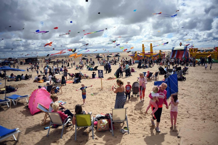 Members of the public relax on the beach as kite enthusiasts participate in the St Annes Kite Festival on the seafront in Lytham St Annes, north west England on July 30, 2016. (OLI SCARFF/AFP/Getty Images)
