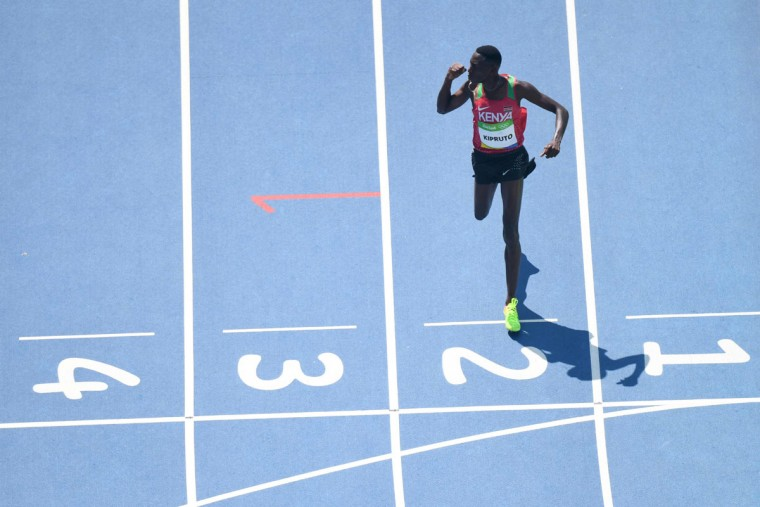 Kenya's Conseslus Kipruto celebrates as he crosses the finish line to win the Men's 3000m Steeplechase Final during the athletics event at the Rio 2016 Olympic Games at the Olympic Stadium in Rio de Janeiro on August 17, 2016. (ANTONIN THUILLIER/AFP/Getty Images)