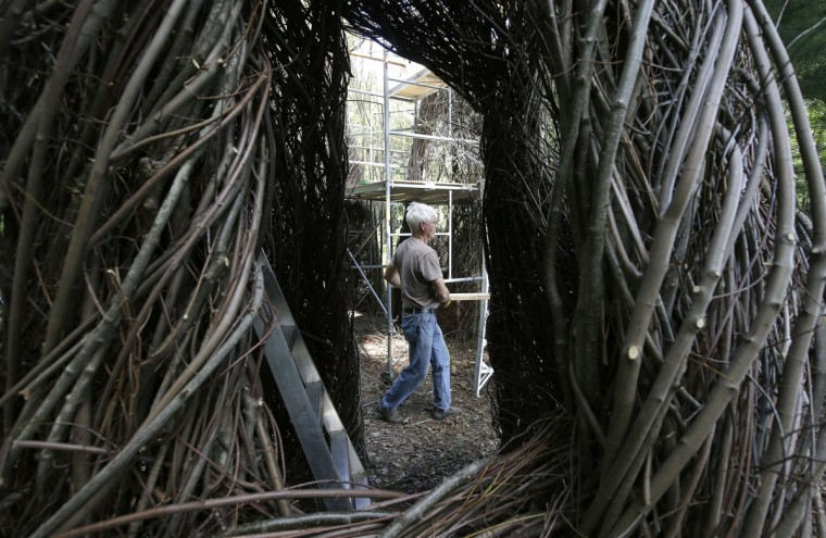 "In this Wednesday, Aug. 17, 2016 photo sculptor Patrick Dougherty carries a piece of scaffolding while constructing a sculptural installation ""The Wild Rumpus,"" from branches and sticks on the grounds of the Tower Hill Botanic Garden, in Boylston, Mass. Dougherty's installation opens to the public Thursday, Aug. 25. (AP Photo/Steven Senne)"