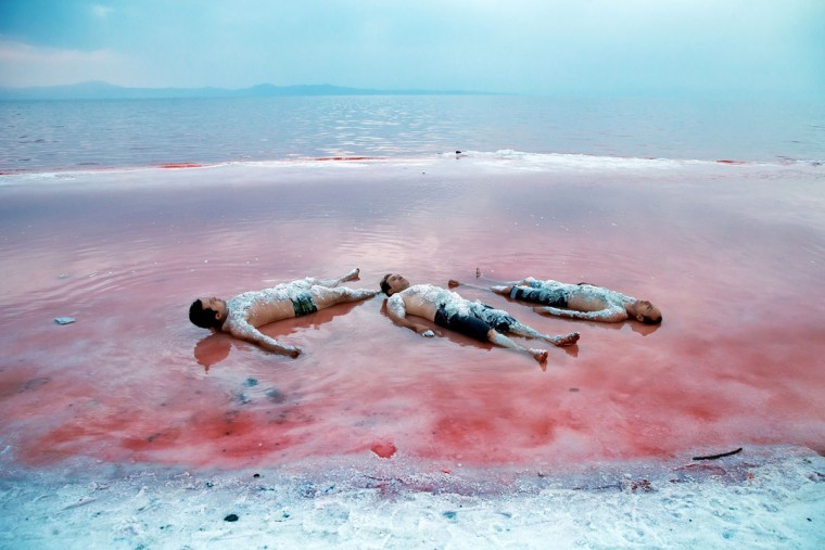 This picture taken on Thursday, Aug. 25, 2016, shows Iranians lying beside Urmia Lake with their bodies covered with salt near Urmia, North-western Iran. Hopes for survival of Urmia salt lake have been revived after more rains boosted a government program aimed at preserving the almost dried up water body. (AP Photo/Ebrahim Noroozi)