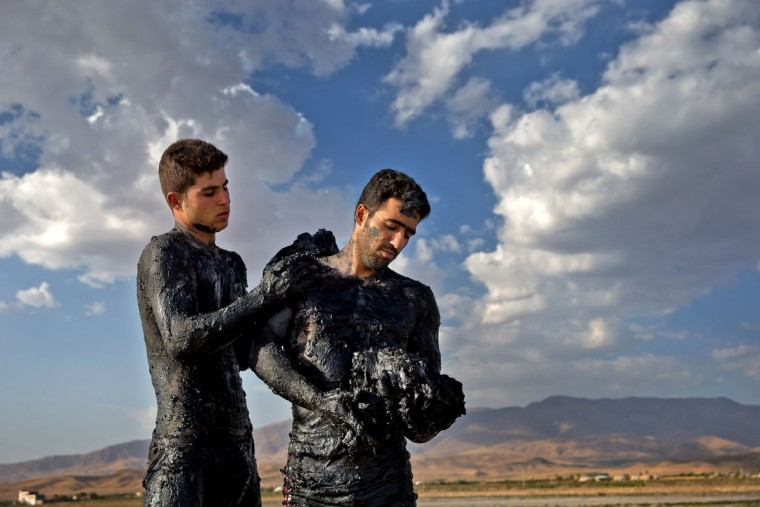 This picture taken on Saturday, Aug. 27, 2016, shows two Iranians covering their bodies with mud near Urmia, North-western Iran. Hopes for survival of Urmia salt lake have been revived after more rains boosted a government program aimed at preserving the almost dried up water body. (AP Photo/Ebrahim Noroozi)