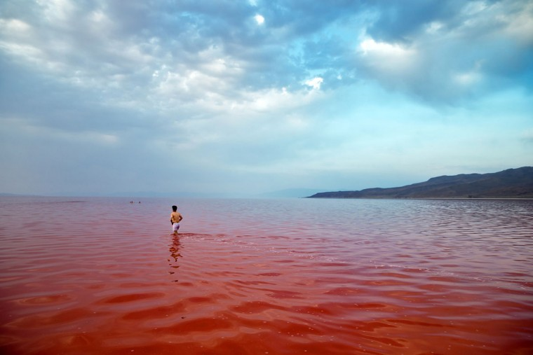 This picture taken on Thursday, Aug. 25, 2016, shows an Iranian spending time in Urmia Lake near Urmia, North-western Iran. Hopes for survival of Urmia salt lake have been revived after more rains boosted a government program aimed at preserving the almost dried up water body. (AP Photo/Ebrahim Noroozi)