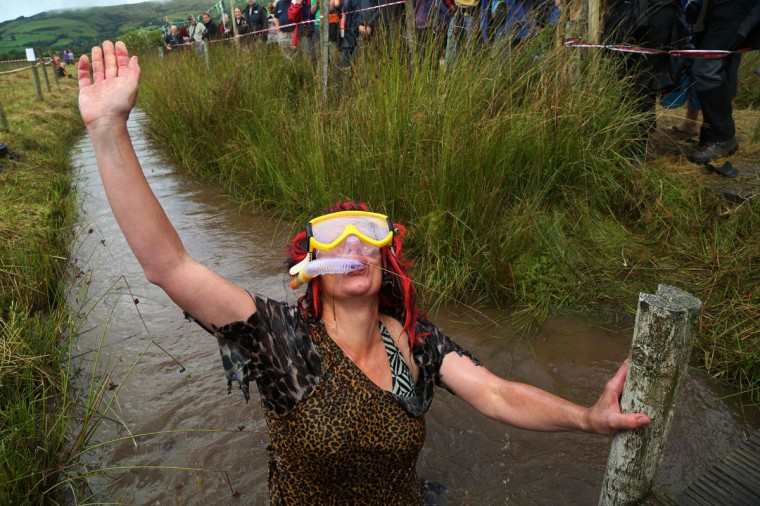 A man dressed as a cavewoman celebrates after completing the course during the World Bog Snorkelling Championships in Waen Rhydd peat bog at Llanwrtyd Wells, south Wales on August 28, 2016. Entrants must negotiate two lengths of a 60-yard trench through the peat bog in the quickest possible time without using any conventional swimming strokes. (GEOFF CADDICK/AFP/Getty Images)