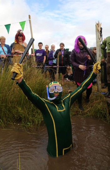 A man dressed as Kickass celebrates after he swims the course in the World Bog Snorkelling Championships in Waen Rhydd peat bog at Llanwrtyd Wells, south Wales on August 28, 2016. Entrants must negotiate two lengths of a 60-yard trench through the peat bog in the quickest possible time without using any conventional swimming strokes. (GEOFF CADDICK/AFP/Getty Images)