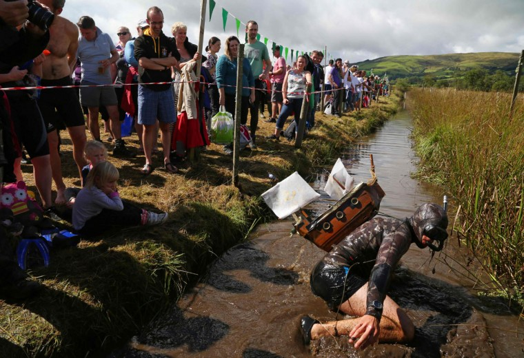 A competitor swims with a model of a galleon on his back as he takes part in the World Bog Snorkelling Championships in Waen Rhydd peat bog at Llanwrtyd Wells, south Wales on August 28, 2016. Entrants must negotiate two lengths of a 60-yard trench through the peat bog in the quickest possible time without using any conventional swimming strokes. (GEOFF CADDICK/AFP/Getty Images)