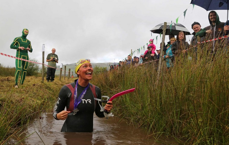 A Swedish competitor celebrates a time of 1 minute 33 seconds after she swims the course during the World Bog Snorkelling Championships in Waen Rhydd peat bog at Llanwrtyd Wells, south Wales on August 28, 2016. Entrants must negotiate two lengths of a 60-yard trench through the peat bog in the quickest possible time without using any conventional swimming strokes. (GEOFF CADDICK/AFP/Getty Images)