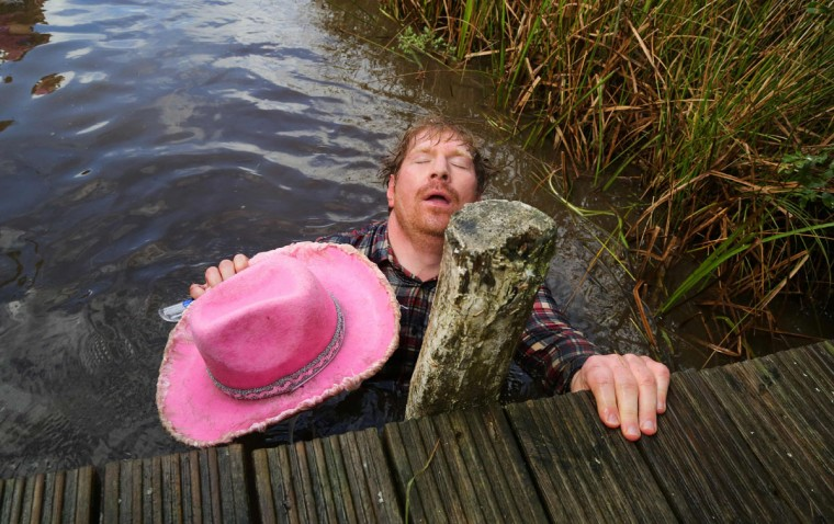 A man dressed as a cowboy lies back exhausted after he swims the course during the World Bog Snorkelling Championships in Waen Rhydd peat bog at Llanwrtyd Wells, south Wales on August 28, 2016. Entrants must negotiate two lengths of a 60-yard trench through the peat bog in the quickest possible time without using any conventional swimming strokes. (GEOFF CADDICK/AFP/Getty Images)