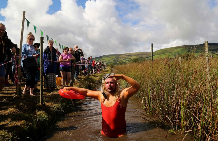 A man dressed as a lifeguard celebrates after he swims the course during the World Bog Snorkelling Championships in Waen Rhydd peat bog at Llanwrtyd Wells, south Wales on August 28, 2016. Entrants must negotiate two lengths of a 60-yard trench through the peat bog in the quickest possible time without using any conventional swimming strokes. (GEOFF CADDICK/AFP/Getty Images)