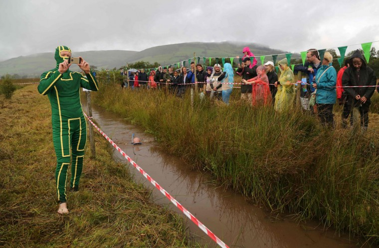 A man dressed as Kickass takes a photograph as a competitor swims the course during the World Bog Snorkelling Championships in Waen Rhydd peat bog at Llanwrtyd Wells, south Wales on August 28, 2016. Entrants must negotiate two lengths of a 60-yard trench through the peat bog in the quickest possible time without using any conventional swimming strokes. (GEOFF CADDICK/AFP/Getty Images)