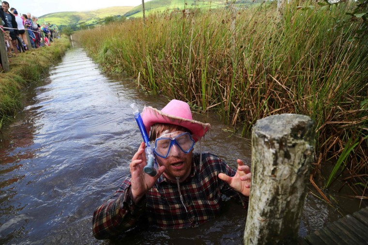 A man dressed as a cowboy celebrates after he swims the course during the World Bog Snorkelling Championships in Waen Rhydd peat bog at Llanwrtyd Wells, south Wales on August 28, 2016. Entrants must negotiate two lengths of a 60-yard trench through the peat bog in the quickest possible time without using any conventional swimming strokes. (GEOFF CADDICK/AFP/Getty Images)