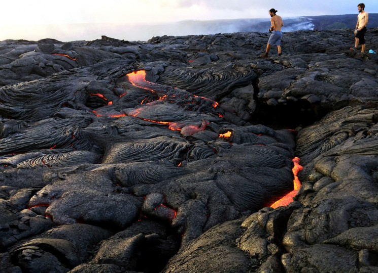 In this Monday, Aug. 8, 2016 photo, lava from Kilauea, an active volcano on Hawaii's Big Island, flows toward the ocean in Volcanoes National Park near Kalapana, Hawaii. The current lava flow erupted from a vent on the volcano in May and made its way to the sea in late July. Visitors can hike about 10 miles round trip to see the lava, or take a boat or helicopter tour to see the flow. (AP Photo/Caleb Jones)