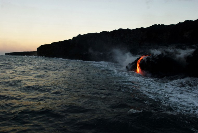 In this Tuesday, Aug. 9, 2016 photo, lava from Kilauea, an active volcano on Hawaii's Big Island, flows into the ocean as seen from a boat operated by Lava Ocean Tours off the coast of Volcanoes National Park near Kalapana, Hawaii. The current lava flow erupted from a vent on the volcano in May and made its way to the sea in late July. Visitors can hike about 10 miles round trip to see the lava flow, or take a boat or helicopter tour to see the flow. (AP Photo/Caleb Jones)