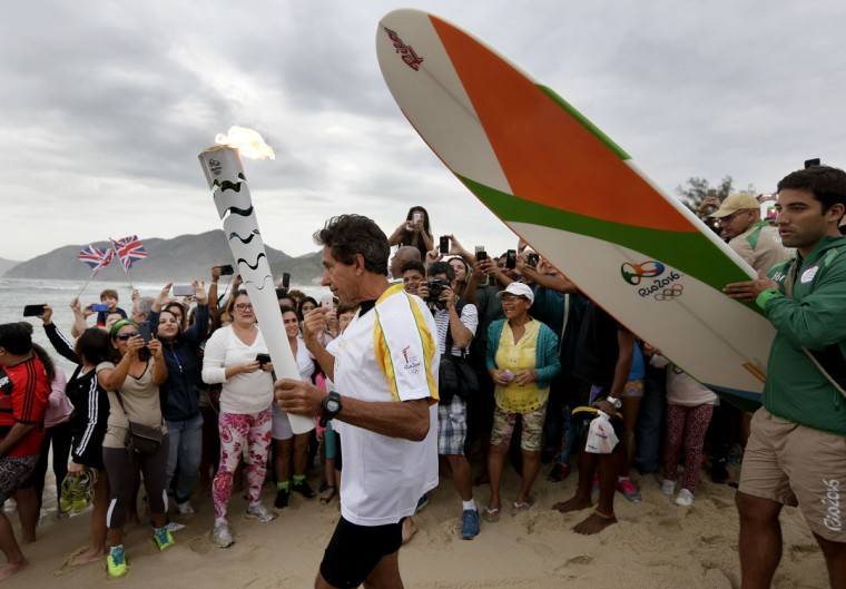 Brazilian Rico de Souza walks to the beach as he prepares to surf with the Olympic torch at Macumba beach as the torch relay continues on its journey to the opening ceremony of Rio's 2016 Summer Olympics, in Rio de Janeiro, Brazil, Thursday, Aug. 4, 2016. (AP Photo/Charlie Riedel)