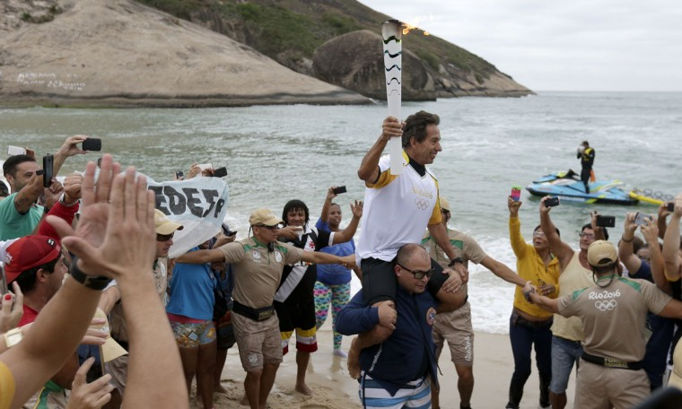 Brazilian Rico de Souza celebrates with the crowd after surfing with the Olympic torch at Macumba beach as the torch relay continues on its journey to the opening ceremony of Rio's 2016 Summer Olympics, in Rio de Janeiro, Brazil, Thursday, Aug. 4, 2016. (AP Photo/Charlie Riedel)