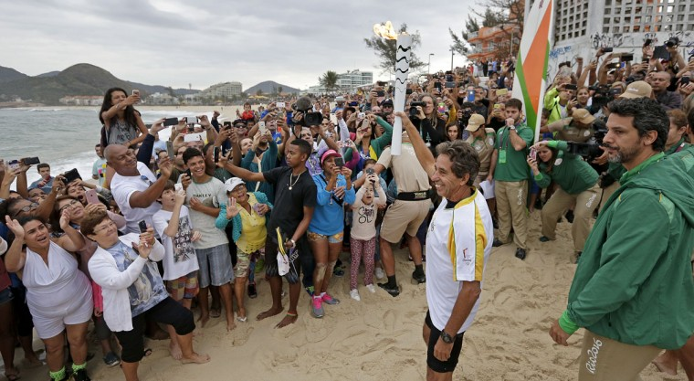 Brazilian Rico de Souza celebrates with the crowd as he prepares to surf with the Olympic torch at Macumba beach as the torch relay continues on its journey to the opening ceremony of Rio's 2016 Summer Olympics, in Rio de Janeiro, Brazil, Thursday, Aug. 4, 2016. (AP Photo/Charlie Riedel)