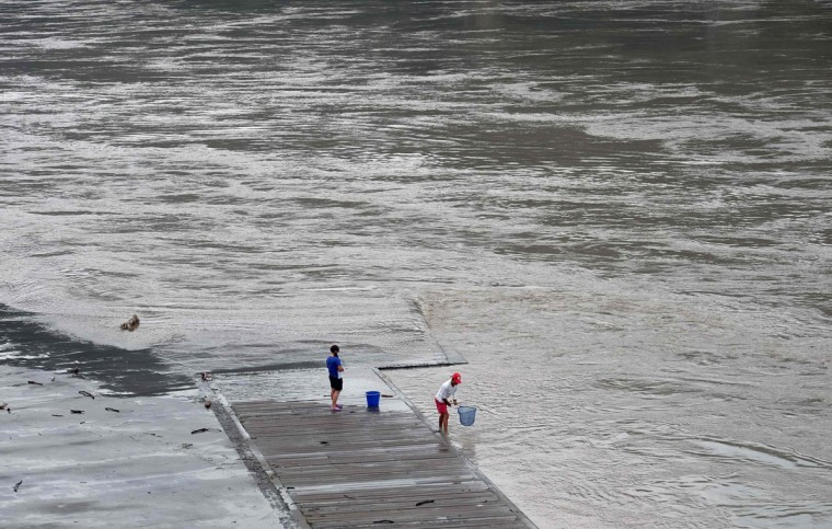 Local residents catch fish from the Xindian river after typhoon Megi passed at Xindian district in New Taipei City on September 28, 2016. Typhoon Megi hit the Chinese mainland early in the morning on September 28 killing one, after leaving a trail of destruction in Taiwan, where four are dead and a million still without power. (SAM YEH/AFP/Getty Images)
