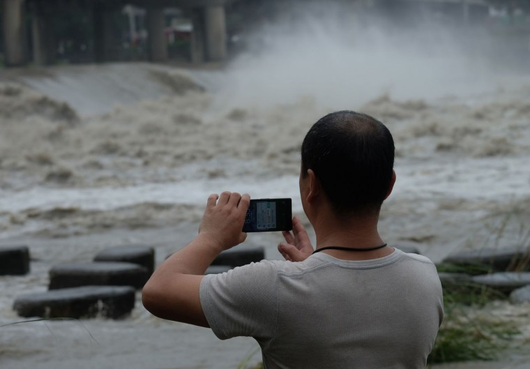 A local resident takes a photo at Xindian river in the aftermath of typhoon Megi at Xindian district in New Taipei City on September 28, 2016. Typhoon Megi hit the Chinese mainland early in the morning on September 28 killing one, after leaving a trail of destruction in Taiwan, where four are dead and a million still without power. (SAM YEH/AFP/Getty Images)