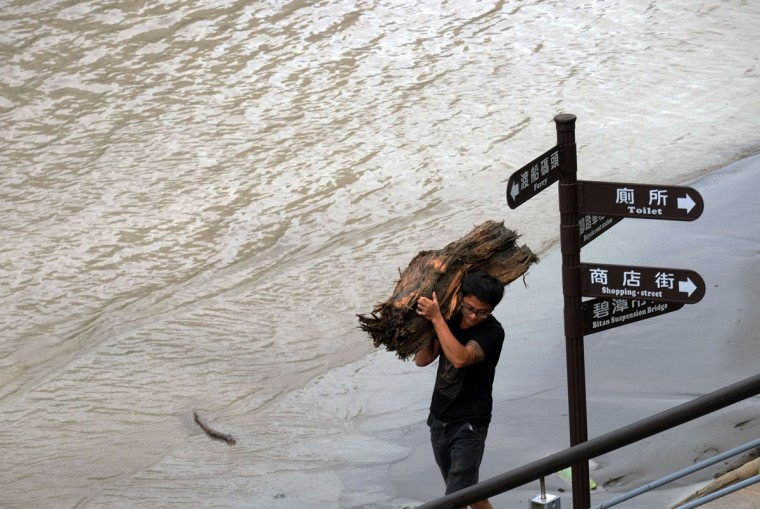 A local resident carries wood washed up by strong winds of typhoon Megi at Xindian district in New Taipei City on September 28, 2016. Typhoon Megi hit the Chinese mainland early in the morning on September 28 killing one, after leaving a trail of destruction in Taiwan, where four are dead and a million still without power. (SAM YEH/AFP/Getty Images)