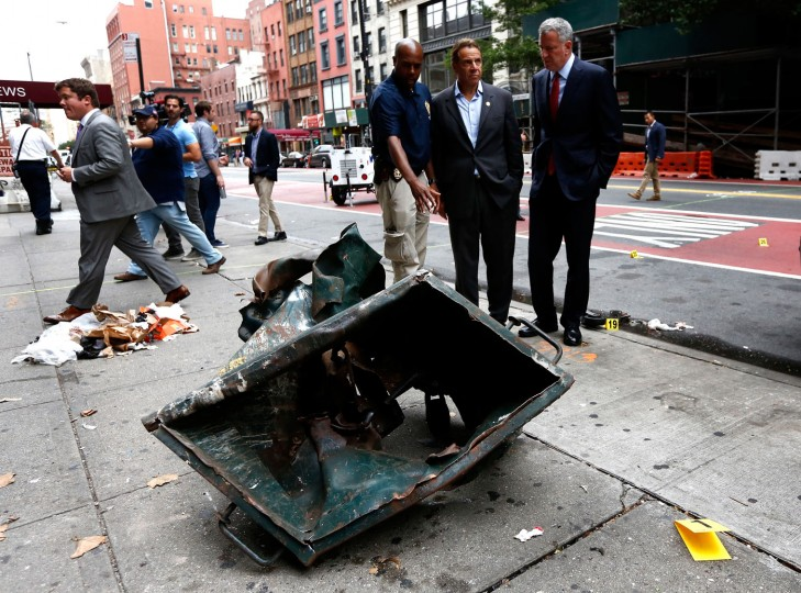 "New York Mayor Bill de Blasio (R) and New York Governor Andrew Cuomo (C) stand in front of a mangled dumpster while touring the site of an explosion that occurred on Saturday night on September 18, 2016 in the Chelsea neighborhood of New York City. An explosion in a construction dumpster that injured 29 people is being labeled an ""intentional act"". A second device, a pressure cooker, was found four blocks away that an early investigation found was likely also a bomb. (Photo by Justin Lane-Pool/Getty Images)"