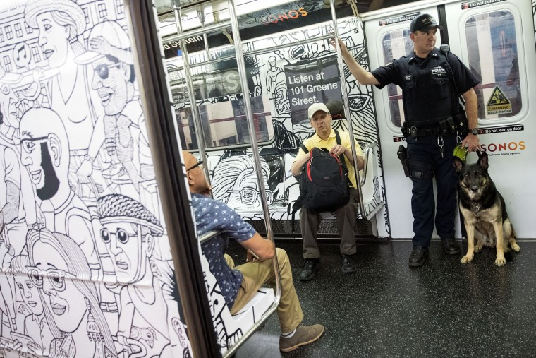 A member of the New York City Police Department K-9 Unit patrols on a subway train between Grand Central Terminal and Times Square, September 18, 2016 in New York City. Following Saturday night's explosion in the Chelsea neighborhood of Manhattan, Mayor Bill de Blasio has promised a 'substantial' police presence throughout the week. New York Governor Andrew Cuomo also said an additional 1,000 New York State and National Guard troops will patrol transit stations and airports as a precaution. (Photo by Drew Angerer/Getty Images)