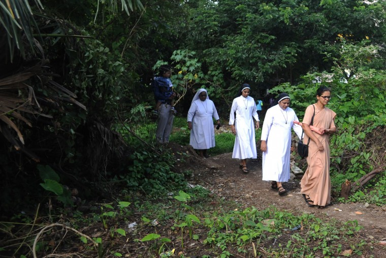 Indian nuns walk through a wooded area to attend a special mass in honour of Mother Teresa at the St. Mother Teresa Church in Virar some 72 km north of Mumbai on September 4, 2016, as she was being canonised at the Vatican. Pope Francis on September 4 proclaimed Mother Teresa a saint, hailing her work with the destitute of Kolkata as a beacon for mankind and testimony of God's compassion for the poor. The revered nun's elevation to Roman Catholicism's celestial pantheon came in a canonisation mass in St Peter's square presided over by Pope Francis in the presence of 100,000 pilgrims. (AFP PHOTO / INDRANIL MUKHERJEE)